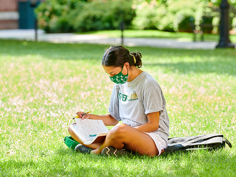 Female student on the quad wearing a mask and reading.