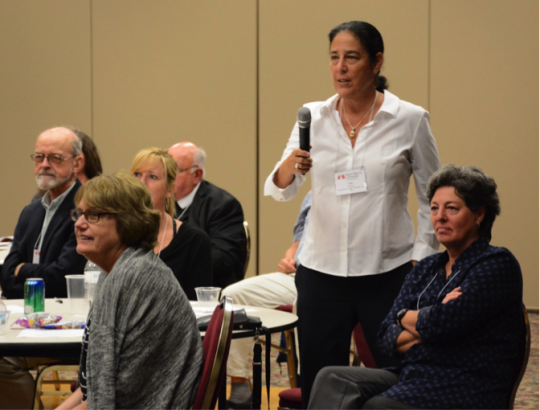 faculty ask a panelist questions at international symposium