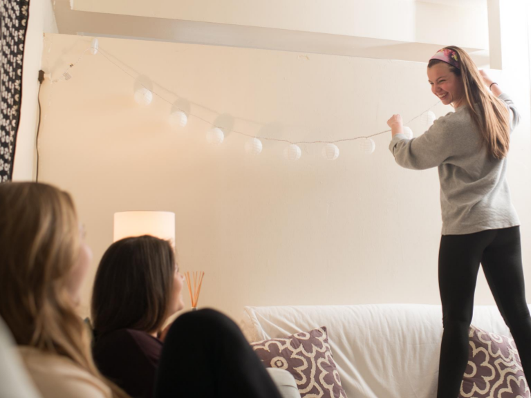 female student hanging fairy lights along dorm room wall